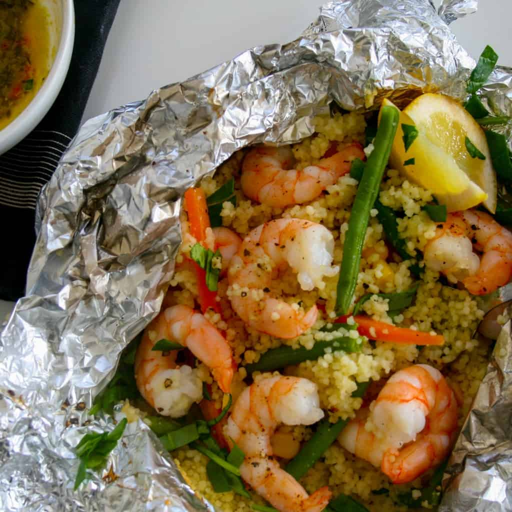 Are you ready to try something new? Give these easy, 30 minute, all-in-one foil wrapped dinners a go. Shrimp with fresh vegetables & seasoned cous cous all smothered in parsley, lemon and garlic sauce and tightly wrapped (to seal in that flavour) in individual foil packets.